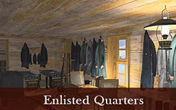 The images in this gallery provide a panoramic view of the enlisted quarters. Narrow beds line both walls. A long table with chairs runs down the center of the space. Rifles are visible in a rack and clothing is hung on hooks along the walls. The room is lit by sunlight and kerosene lamps.