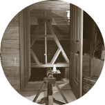 A small circular image containing an image of Kater's Pendulum as seen from the officer's quarters inside the expedition house. The pendulum hangs in an 'A' shaped wooden frame inside one of the lean to structures at each end of the house. Clicking this image will start the 'Katers Pendulum game'