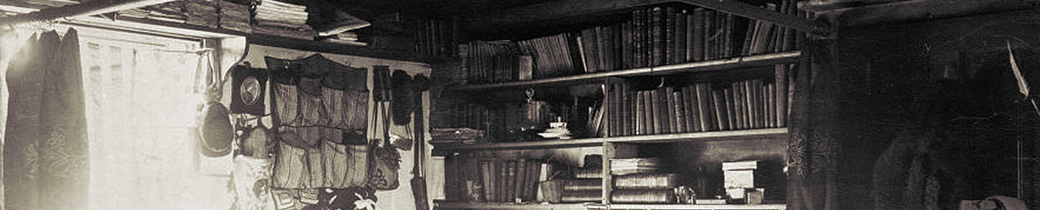A historic photograph showing the crowded but neatly organized living area of Lt. Adolphus Greely. Books, clothing, and scientific instruments hang from walls and bookcases.