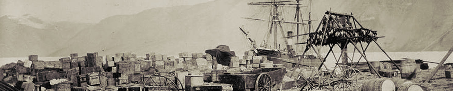 A historic photograph showing expedition supplies on the beach at Fort Conger.