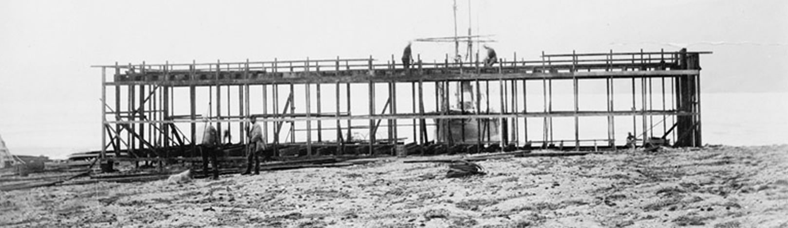 Historic image of Lady Franklin Bay Expedition House under construction. The bow of the Proteus is visible in Discovery Harbor. Two figures stand on the wooden frame of the building. One figure is visible near the sill plate.