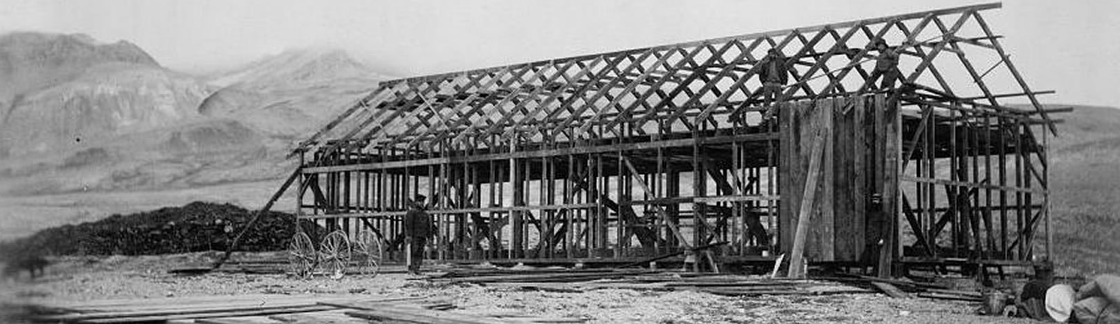 Historic photograph showing the completed house frame of the Lady Franklin Bay Expedition headquarters. In this photograph, the arched roof has been completed. Two figures stand on the roof frame adding wall boards.