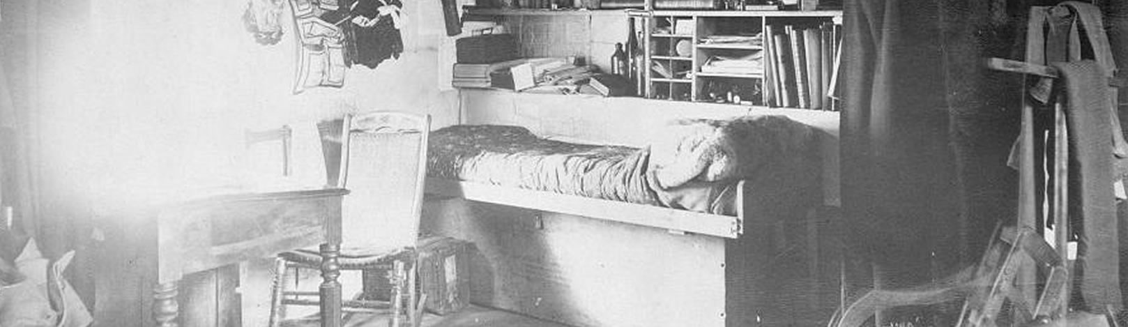Historic photograph of Greely's quarters, showing his bed, desk, and bookshelves. A window near the desk illuminates the room.