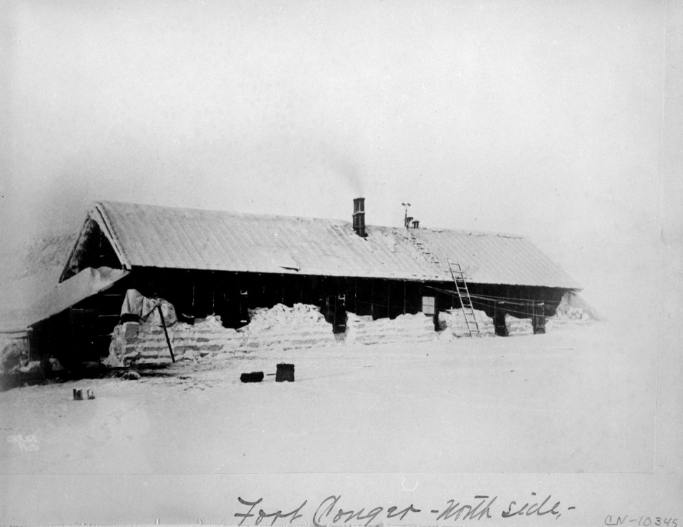 A historic photograph showing the Lady Franklin Bay Expedition house in winter. The long single store structure has snow  banked against the walls, and a ladder leads to the roof.