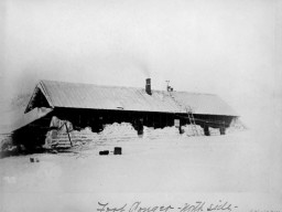 A historic photograph of the Lady Franklin Bay Expedition House, with snow banked around the walls of dwelling, and a ladder leading up to the roof.