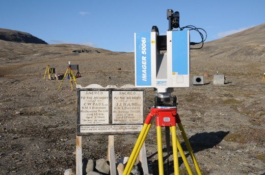 A photograph showing the laser scanner sitting atop its tripod. The scanner is rectangular in shape. In the distance are two tripods with circular target.