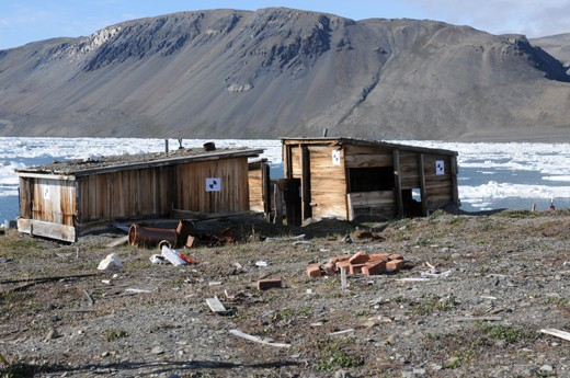 A contemporary photograph of Peary's hut complex, which appears as three small wooden buildings. Ice in Discovery harbor is visible in the distance, and the sky is blue.