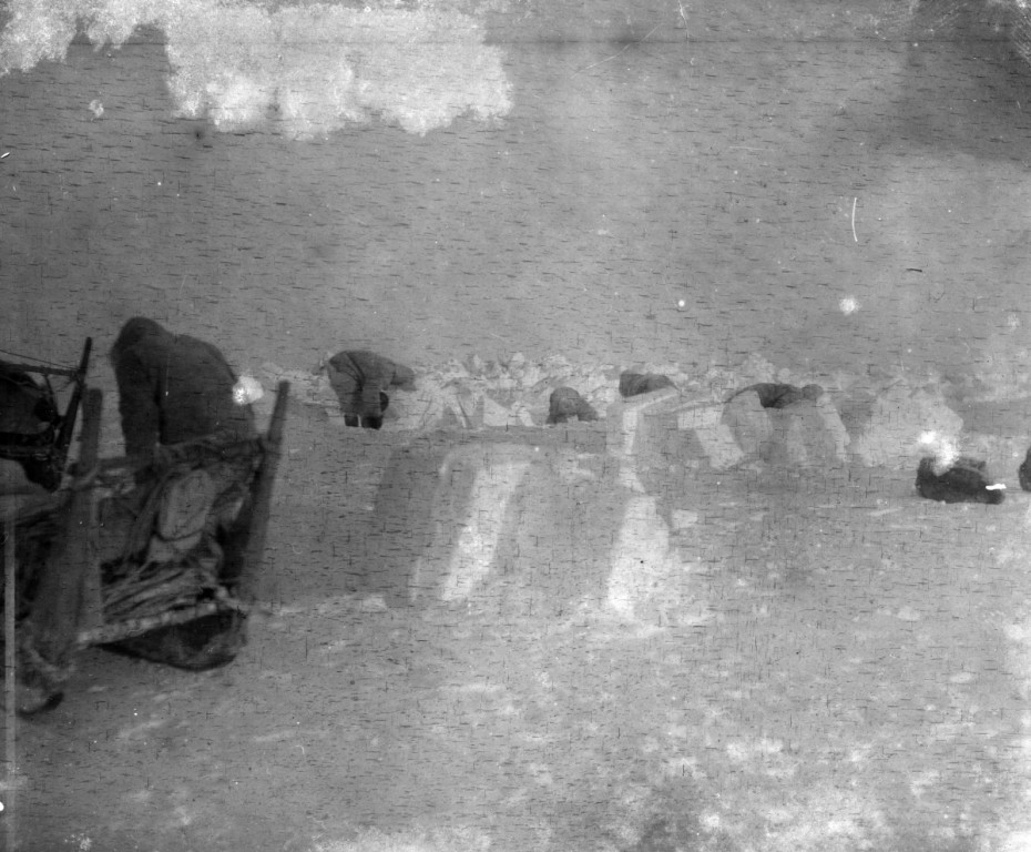 Peary's Inughuit assistants build a snow house or igloo. The structure is under construction and only half built in this historic photograph.