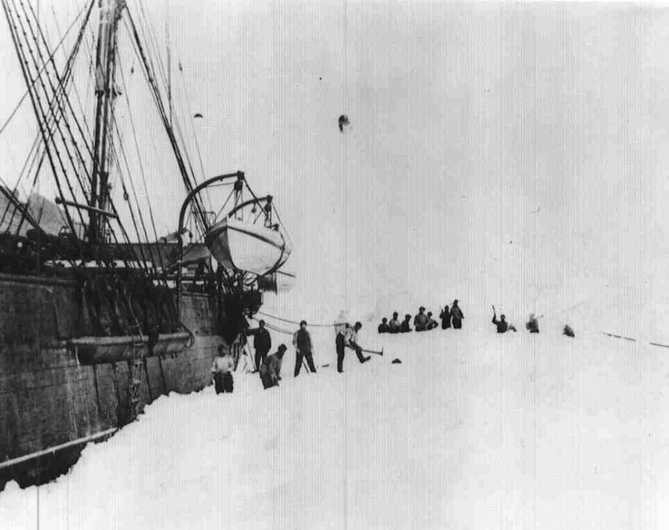 A historic photograph of HMS Discovery in ice, with members of the expedition standing beside her.