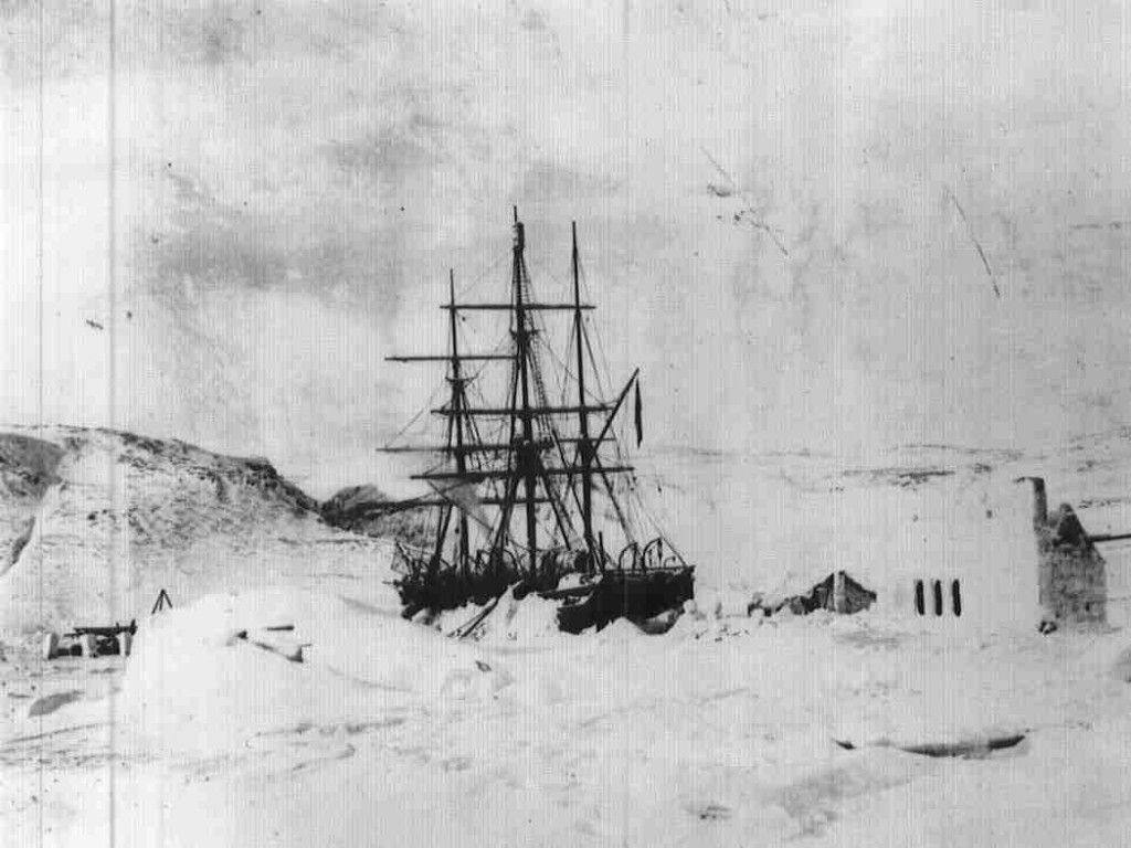 A historic photograph of HMS Discovery in ice, with members of the expedition standing beside her