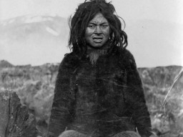 A historic photograph of an Inuit guide, who wears traditional skin and hide clothing.
