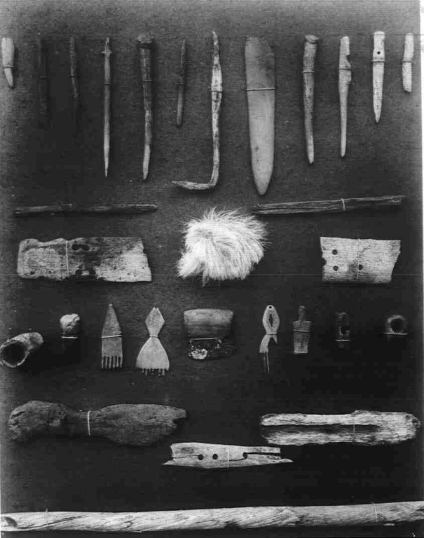 A black and white photograph of Inuit artifacts recovered by the Lady Franklin Bay Expedition. The artifacts include bone and antler harpoons, combs, hooks, and awls.
