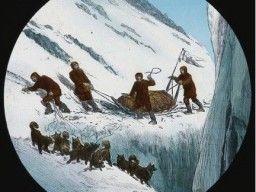 A historic illustration showing a group of men and dogs precariously driving a sledge along a narrow ridge.