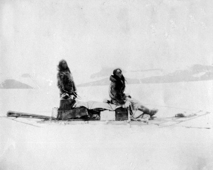 A historic photograph of an Inuit man and woman sledging across an arctic landscape.