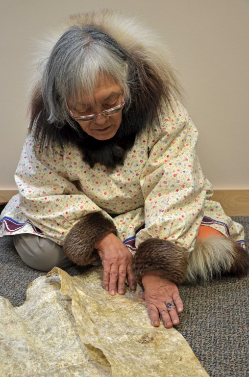 A photograph showing an Inuit woman using the length and width of her hands to measure and cut a piece of hide. The woman is seated and has her hands on the hide.