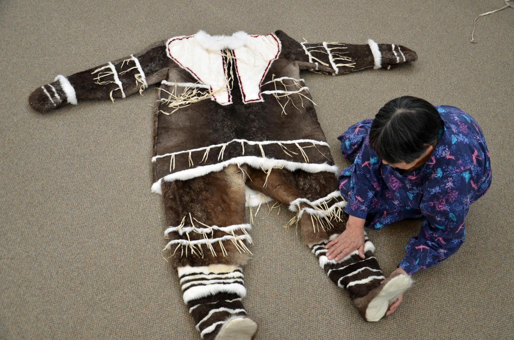 A photograph of an Inuit woman seated beside a beautiful and ornate apkuamiut dance costume. The parka and pants are made from brown colored hide, with white fur trim around the cuffs, pant legs and collar.