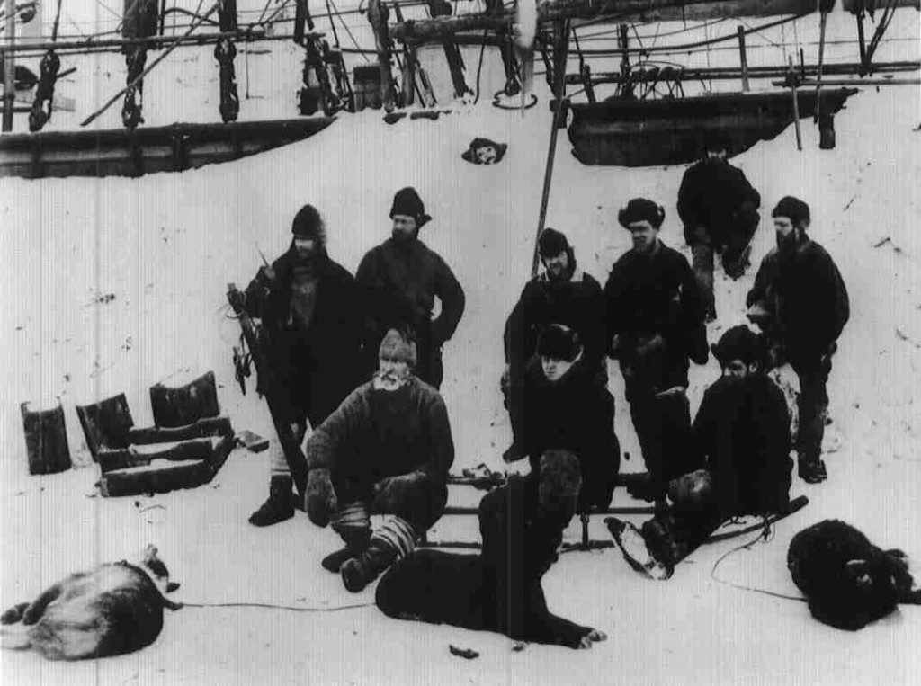 A historic photograph showing members of the British Arctic Expedition posing near their ship. The men are wearing standard issue cotton, canvas and wool clothing.